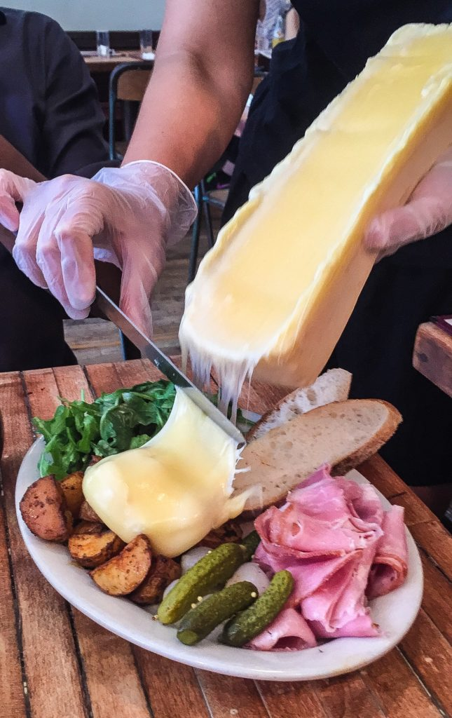 Suisse   $18.00/Regular $23.00/Large Add $4 for Raw Cheese   Raclette cheese, melted and scraped tableside; choice of viande séchée, prosciutto di Parma OR jambon de Paris; roasted potatoes; cornichons; pickled white pearl onions; sliced baguette; arugula salad with champagne vinaigrette