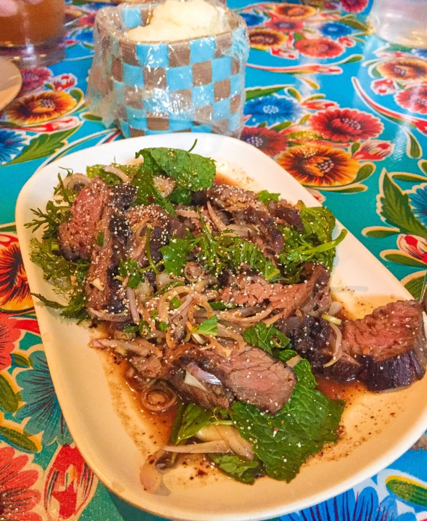 "Neua Naam Tok  18 Spicy Isaan flank steak ""salad"" with fish sauce, lime and chili powder dressing, shallots, lemongrass, mint, cilantro and toasted rice powder. You'll want to get some sticky rice, it's hot. Try it with Beer Lao!"