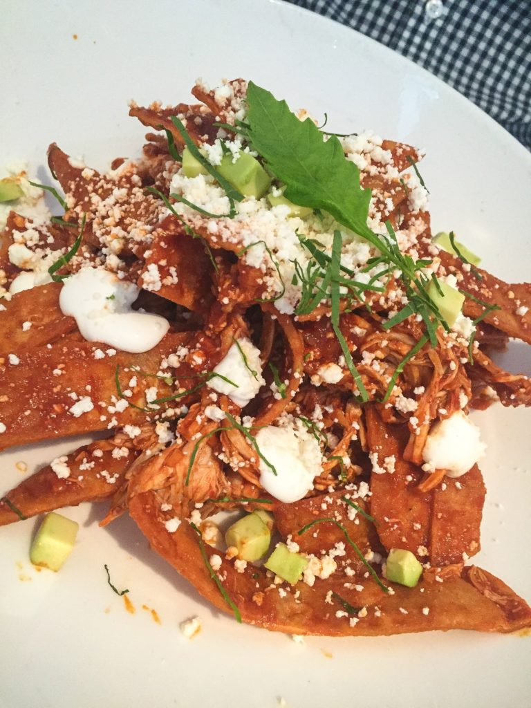 CHILAQUILES ROJOS Corn tortillas lightly fried in salsa roja, onion, cream, queso fresco, avocado with Chicken.